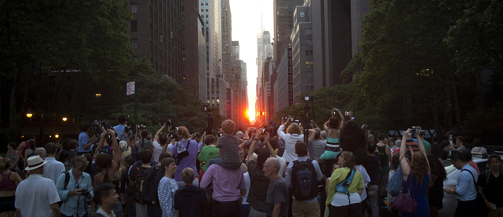 People crowd a bridge that goes over 42nd Street as they take photos of the 'Manhattanhenge' phenomenon in the Manhattan borough of New York July 11, 2014. Manhattanhenge, coined by astrophysicist Neil deGrasse Tyson, occurs twice a year, when the setting sun aligns itself with the east-west grid of streets in Manhattan. REUTERS/Carlo Allegri (UNITED STATES - Tags: SOCIETY CITYSCAPE ENVIRONMENT) - GM2EA7C0P9401