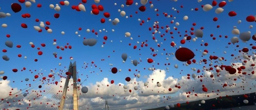 Red and white balloons are released during the opening ceremony of newly built Yavuz Sultan Selim bridge, the third bridge over the Bosphorus linking the city's European and Asian sides in Istanbul, Turkey, August 26, 2016. REUTERS/Murad Sezer - S1BETXRNXHAB