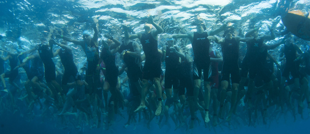 Amateur triathletes wait for the start of the 2.4 miles (3.86 km) swim portion during the Ironman World Championship in Kailua-Kona, Hawaii, October 12, 2013.