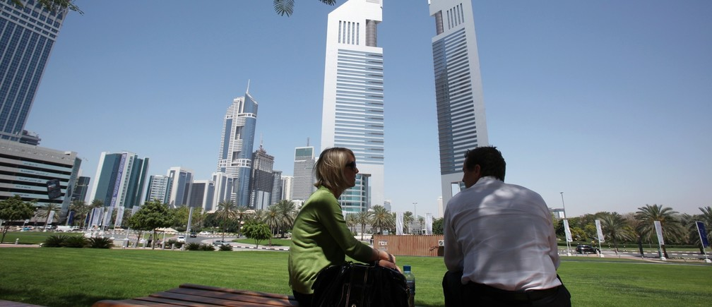 People sit on a bench in front of the Emirates Towers at the Dubai International Financial Centre March 21, 2010.
