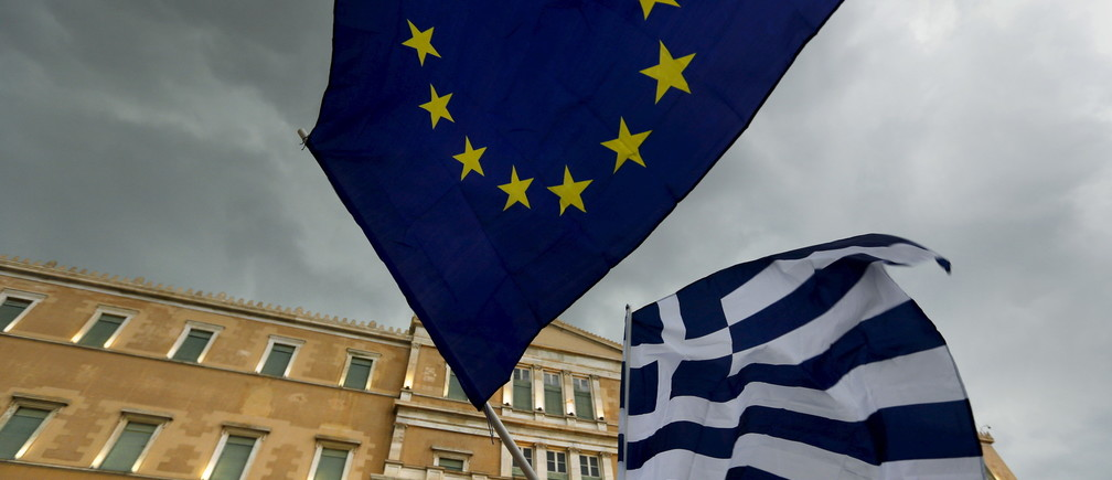 Protesters wave Greek and EU flags during a pro-Euro rally in front of the parliament building, in Athens, Greece, June 30, 2015. Greece's conservative opposition warned on Tuesday that Sunday's vote over international bailout terms would be a referendum over the country's future in Europe, and that wages and pensions would be threatened if people were to reject the package. REUTERS/Yannis Behrakis  - GF10000144934