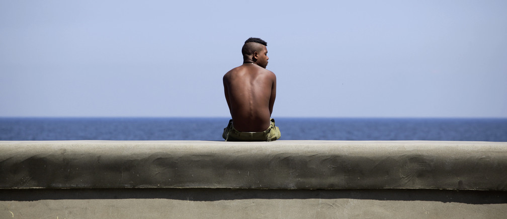 A youth sits on Havana's seafront boulevard 'El Malecon' May 21, 2013. REUTERS/Desmond Boylan (CUBA - Tags: SOCIETY) - GM1E95M09CE01