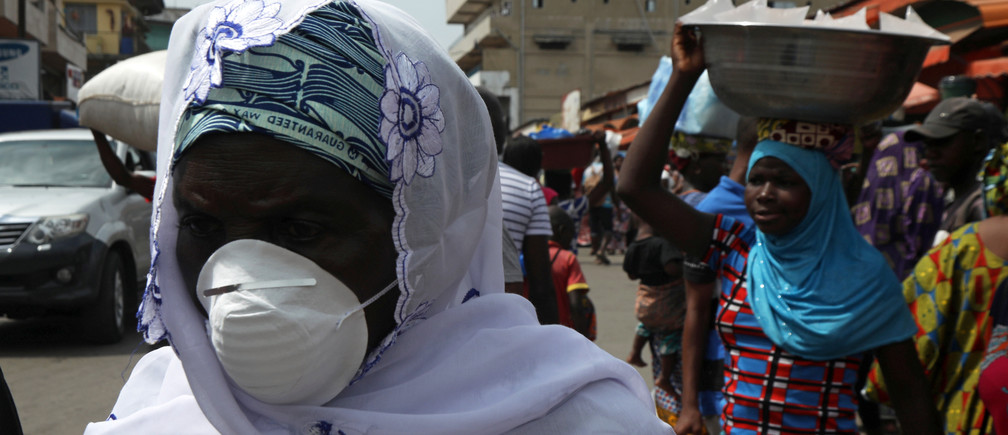 A woman wears a protective mask as she walks on a street in Abidjan, Ivory Coast.