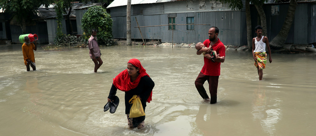 People cross a flooded road in Jamalpur, Bangladesh, July 22, 2019. Picture taken July 22, 2019. REUTERS/Mohammad Ponir Hossain     TPX IMAGES OF THE DAY - RC181D7AAB50