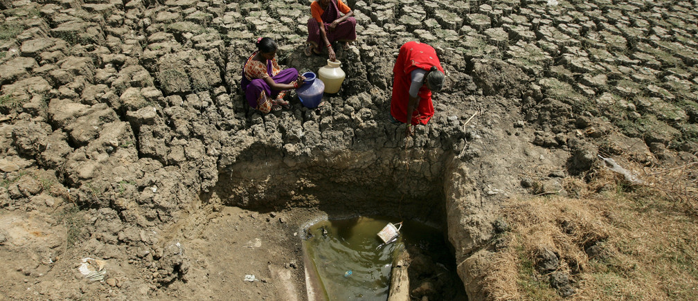 Women fetch water from an opening made by residents at a dried-up lake in Chennai, India, June 11, 2019. REUTERS/P. Ravikumar - RC1B21F03240