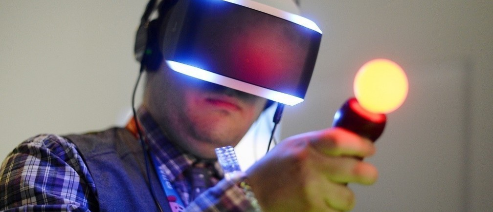 An attendee tries out Sony's Morpheus virtual reality headset at the 2014 Electronic Entertainment Expo, known as E3, in Los Angeles, California June 10, 2014. There has been a rising interest in virtual reality platforms among publishers and developers, who hope the years-old technology -- which creates a 360-degree view that immerses players in fantasy settings -- can finally become a viable platform to reverse shrinking video game industry revenues and draw a new generation of users. Picture taken June 10.             REUTERS/Kevork Djansezian  (UNITED STATES - Tags: BUSINESS SCIENCE TECHNOLOGY) - RTR3TTXU