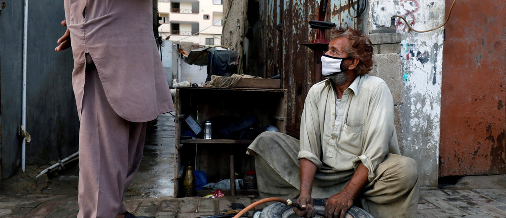 A labourer wearing protective face mask fills air in a tyre at a workshop along a road, as the outbreak of the coronavirus disease (COVID-19) continues, in Karachi, Pakistan, June 12, 2020. REUTERS/Akhtar Soomro     TPX IMAGES OF THE DAY - RC2R7H9Q8KZW