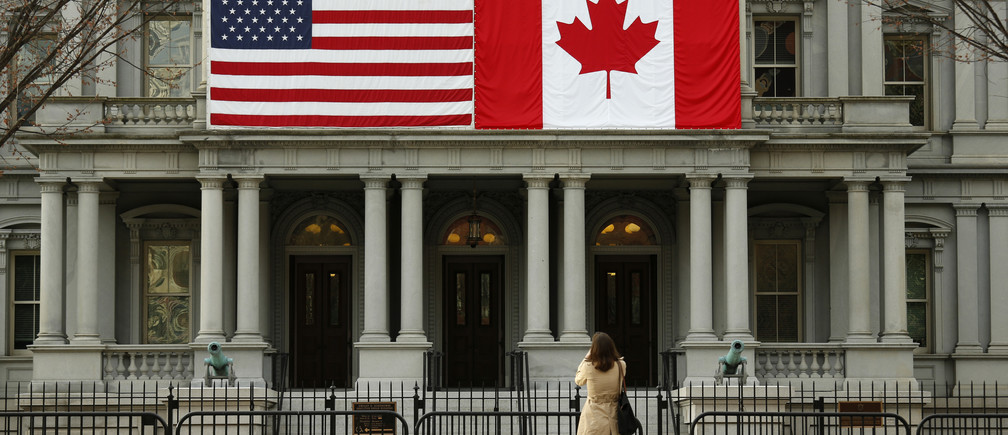 A woman stops to take a photo of the U.S. and Canadian flags placed side-by-side on the Eisenhower Executive Office Building next to the White House in Washington March 8, 2016.  Preparations are under way for the official state visit of Canada's Prime Minister Justin Trudeau on Thursday. REUTERS/Kevin Lamarque - D1AESRIMGHAB