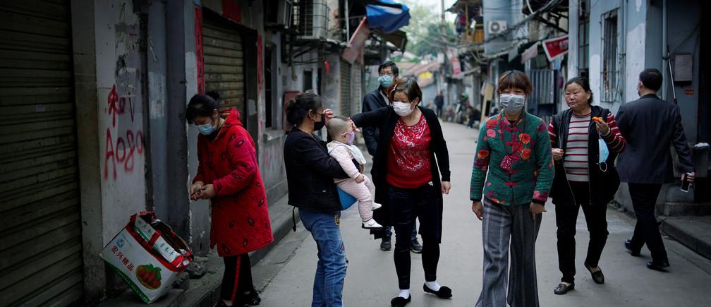 Residentes con máscaras faciales caminan en una antigua comunidad residencial bloqueada por barreras en Wuhan, provincia de Hubei, el epicentro del brote de la enfermedad coronavirus de China (COVID-19), el 5 de abril de 2020.