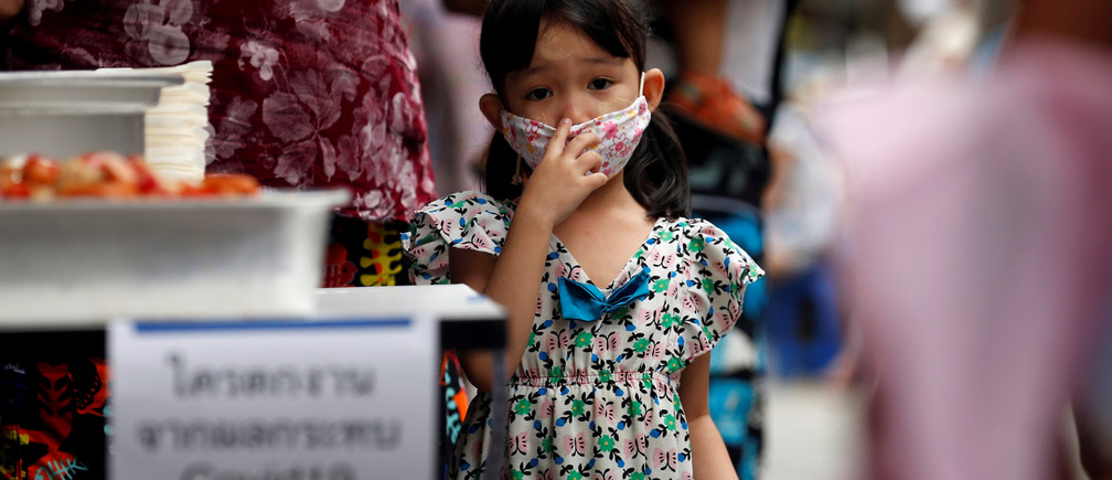 A girl of one of the migrant workers family from Myanmar who lost their jobs, lines up for free foods from volunteers following the coronavirus disease (COVID-19) outbreak in Bangkok, Thailand April 23, 2020. REUTERS/Soe Zeya Tun     TPX IMAGES OF THE DAY - RC2BAG9G9LM7