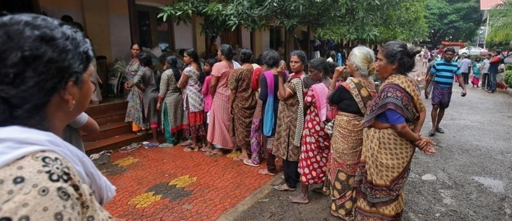 Flood-affected women wait in a queue to receive relief material at a camp in Chengannur in the southern Indian state of Kerala, India, August 20, 2018. REUTERS/Amit Dave - RC1A7478FF80