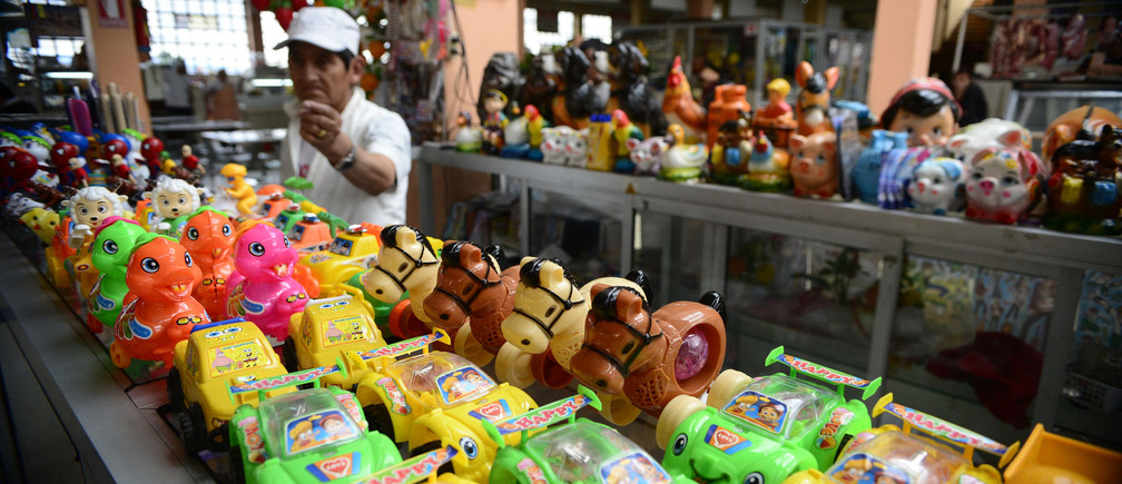 A vendor stands near plastic toys for children at his stall at the Central market in Quito August 26, 2014. The plastic toys cost about 60 cents to $1. Ecuador began using U.S. dollars as legal tender since 2000.  REUTERS/Guillermo Granja (ECUADOR - Tags: BUSINESS) - GM1EA8R0YWD02