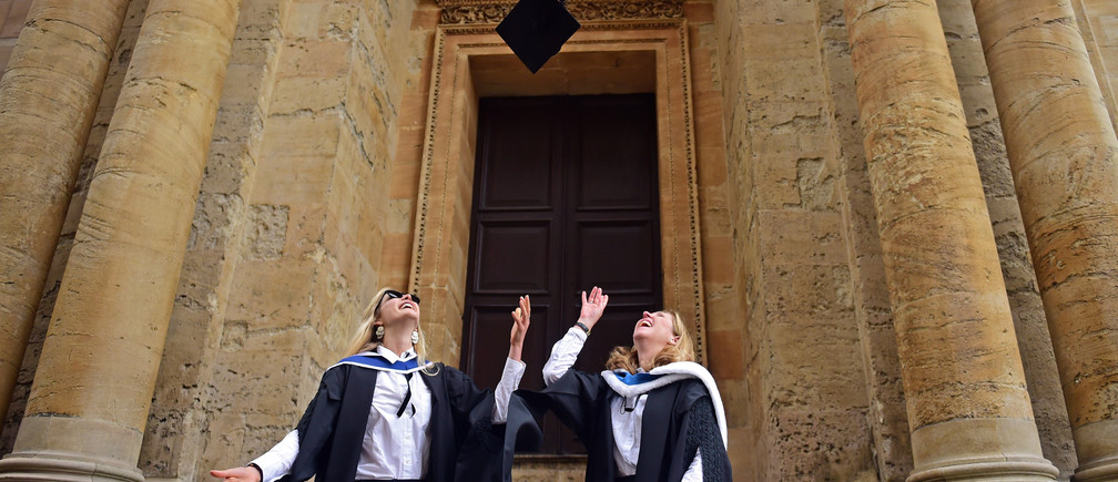 Graduates throw their mortar boards in the air after a graduation ceremony at Oxford University, in Oxford, Britain July 15, 2017. REUTERS/Hannah McKay - RC1383346AE0