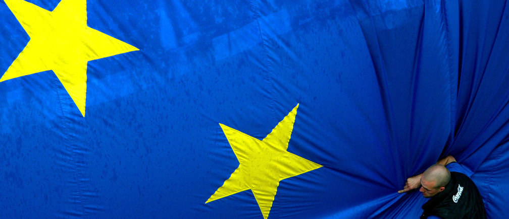 A worker adjusts a 150 metre-square European flag during a celebration in Brussels' Jubilee Park to mark the expansion of the European Union to 25 from 15 states on April 30, 2004. Cyprus, the Czech Republic, Estonia, Hungary, Latvia, Lithuania, Malta, Poland, Slovakia and Slovenia will join the European Union on May 1. UNICS REUTERS/Francois Lenoir Pictures of the Year 2004  FLR/CRB - RP4DRIGNBSAB