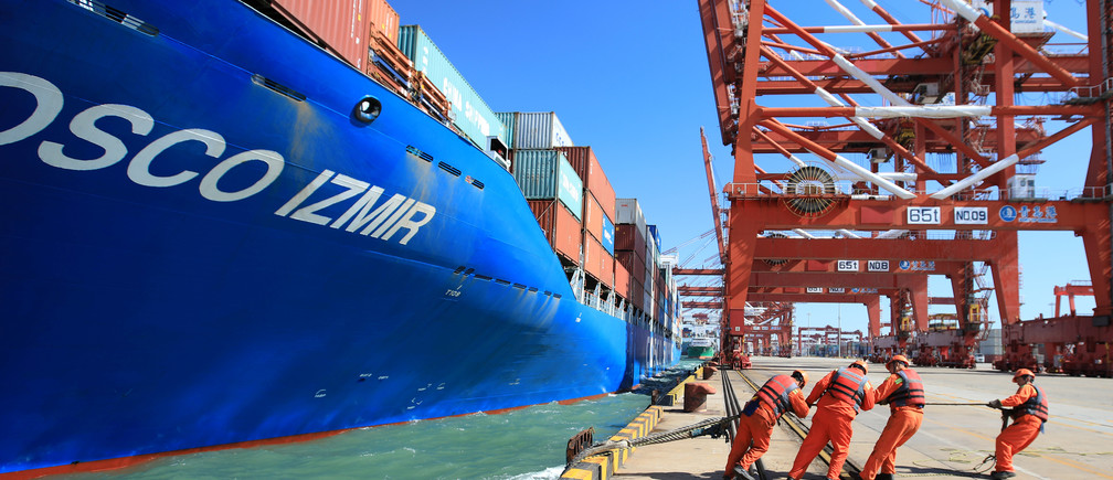 Workers help to dock a China Ocean Shipping Company (COSCO) container ship at a port in Qingdao, Shandong province, China October 19, 2018. REUTERS/Stringer  ATTENTION EDITORS - THIS IMAGE WAS PROVIDED BY A THIRD PARTY. CHINA OUT. - RC13F73989C0