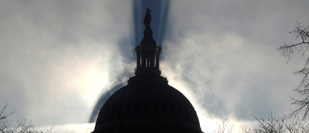 The sun rises through morning fog behind the Statue of Freedom and the US Capitol in Washington, D.C.
