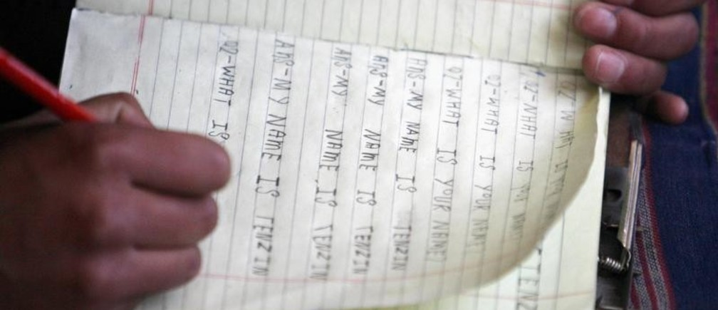 A Tibetan woman in exile who recently arrived in India learns to write English in Dharamsala March 20, 2008.