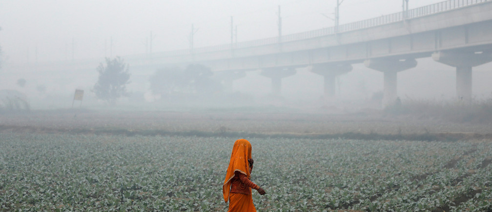 A woman walks across a field on a smoggy morning in New Delhi, India, November 13, 2017.