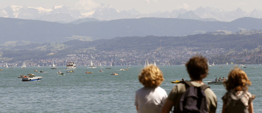 People sit on a wall on the banks of Lake Zurich during sunny summer weather in Zurich July 3, 2011.  REUTERS/Arnd Wiegmann