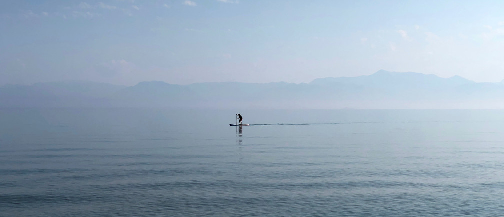 A man paddles in the waters of the Ionian Sea near Sidari settlement on the island of Corfu, Greece July 26, 2019. REUTERS/Vasily Fedosenko - RC1658D738E0