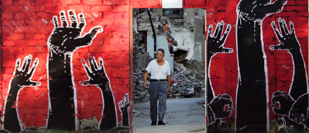A man walks towards a fence that is painted with an advertisement in Shanghai August 2, 2006. The fence covers a district undergoing demolition.  REUTERS/Aly Song (CHINA) - GM1DTELHMRAA