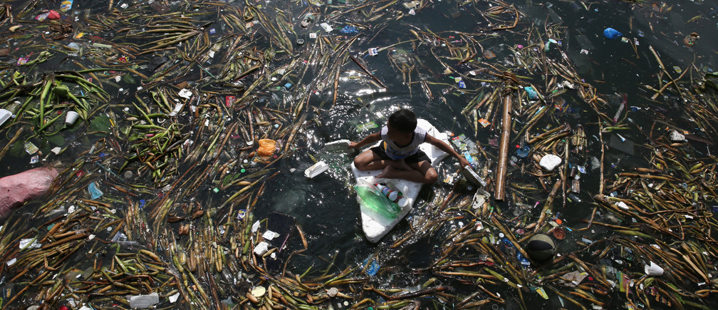 Children float on makeshift raft made of discarded boards and styrofoam as they collect recyclable plastic bottles drifting along the coast of Manila Bay at the slum area in the Baseco Compound in metro Manila, Philippines October 16, 2017. REUTERS/Romeo Ranoco - RC175D36F700