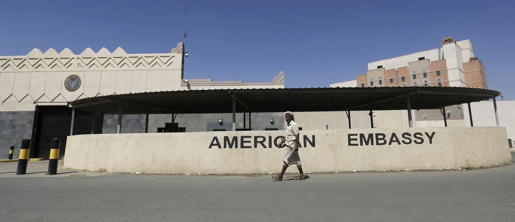 A man walks past the U.S. embassy in Sanaa after the road in front of it was opened by the police March 4, 2015
