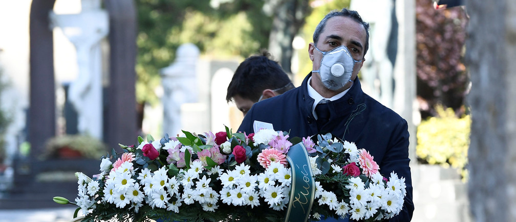 Cemetery workers and funeral agency workers in protective masks transport a coffin of a person who died from coronavirus disease (COVID-19), into a cemetery in Bergamo, Italy March 16, 2020. REUTERS/Flavio Lo Scalzo - RC22LF9DLNKA