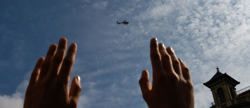 A man holds up his hands as a police helicopter flies overhead during a protest a day after the banned independence referendum in Barcelona, Spain October 2, 2017. REUTERS/Eloy Alonso - RC1F5214D7F0