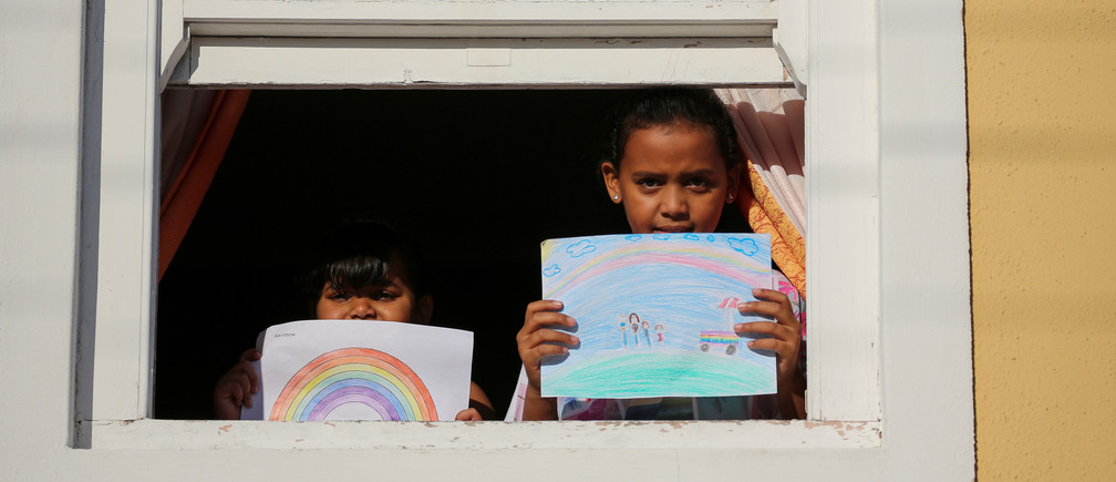 "Bashierah Moos, 5, and Hanaa Moos, 9, pose for a photograph while holding pictures that they drew during the coronavirus disease (COVID-19) outbreak, as they stand by a window at their house in Cape Town, South Africa, April 19, 2020. Bashierah drew a picture of a rainbow and Hanaa said ""I drew my family next to an ice-cream truck because I miss, I miss going out."" She added ""I feel sad because I can't see my friends and go to school."" REUTERS/Sumaya Hisham     SEARCH ""CORONAVIRUS DRAWING"" FOR THIS STORY. SEARCH ""WIDER IMAGE"" FOR ALL STORIES. - RC2BAG92O3MV"