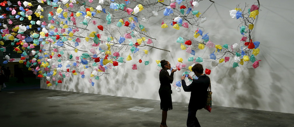 "Visitors take a picture in front of the installation ""Plastic Tree"" by Cameroonian artist Pascale Marthine Tayou at the Art Unlimited exhibition at the Art Basel fair in Basel June 16, 2015. Founded by gallerists in 1970, the Art Basel is an international art show which is held annually in Basel, Hong Kong and Miami Beach. REUTERS/Arnd Wiegmann  FOR EDITORIAL USE ONLY. NOT FOR SALE FOR MARKETING OR ADVERTISING CAMPAIGNS  - GF10000129549"