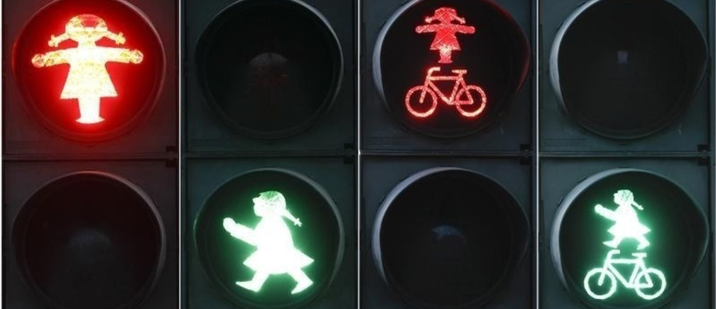 A combination of four pictures show red and green crossing signals for pedestrian and cyclists featuring a woman in the east German town of Fuerstenwalde, south east of Berlin March 7, 2012. The pig-tailed female crossing guard has ousted her traditional, hat-wearing male counterpart inFuerstenwalde in time for International Women's Day on Thursday. REUTERS/Fabrizio Bensch (GERMANY - Tags: SOCIETY TRANSPORT) - RTR2Z05C