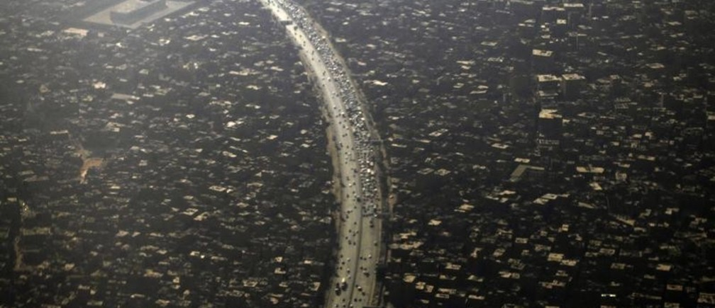 An aerial view of Cairo's traffic and houses is pictured through the window of an airplane September 11, 2013. Egypt's population has reached 85 million with the Cairo governorate coming in with the highest number at 8.9 million people, according to the Central Agency for Public Mobilization and Statistics (CAPMAS). REUTERS/Amr Abdallah Dalsh  (EGYPT - Tags: CITYSCAPE) - GM1E99C05H101