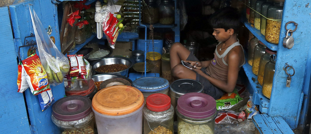 A boy uses a mobile phone as he sits inside his father's snacks shop along a road in Kolkata, India, February 22, 2016. REUTERS/Rupak De Chowdhuri TPX IMAGES OF THE DAY      - D1AESOLORCAA