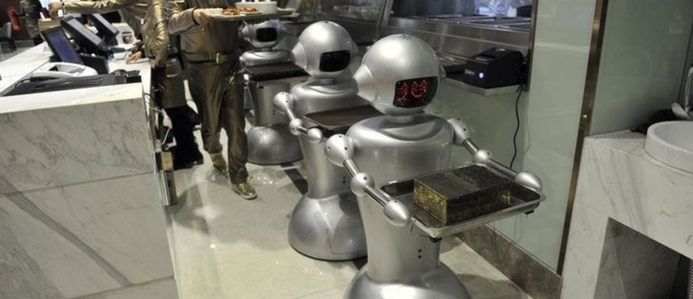 A man puts dishes on robots for delivery at a restaurant in Hefei, Anhui province, December 26, 2014. The restaurant, with a space of 1300 square metres and a total of 30 robots to cook meals, deliver dishes and welcome costumers, was reported to be the biggest robot restaurant in China. REUTERS/STRINGER (CHINA - Tags: SOCIETY BUSINESS FOOD SCIENCE TECHNOLOGY) CHINA OUT. NO COMMERCIAL OR EDITORIAL SALES IN CHINA