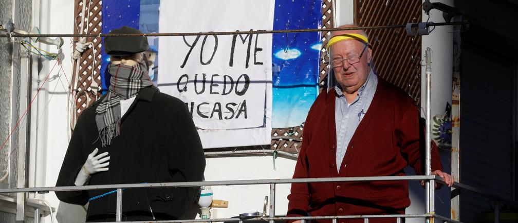 """José María León, de 77 años, lleva un protector facial mientras está de pie en el balcón de su piso, junto a un maniquí vestido y un cartel que dice """"Me quedo en casa"""", durante el brote de la enfermedad coronavirus (COVID-19), en Ronda, al sur de España, el 3 de abril de 2020."""