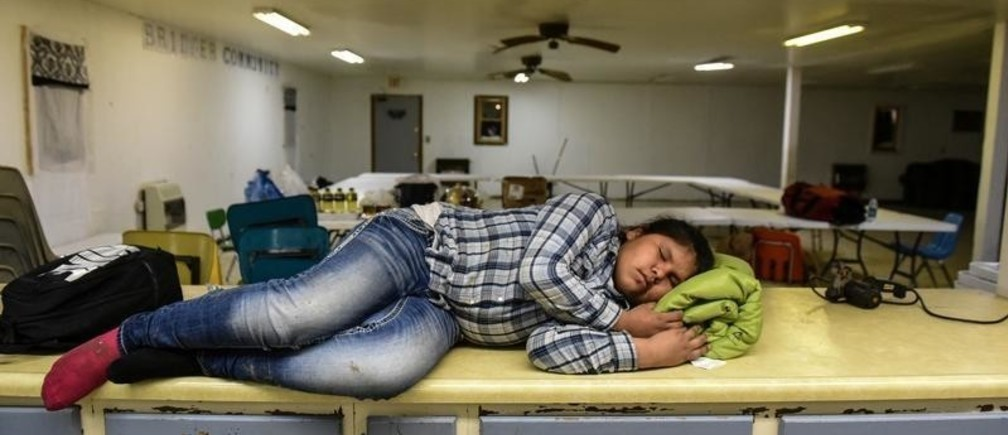 Fronda White, age 10, from the Standing Rock Reservation, one the Fort Laramie treaty riders, falls asleep on the kitchen counter at a community center on the Cheyenne River Reservation in Bridger, South Dakota, U.S., April 15, 2018.