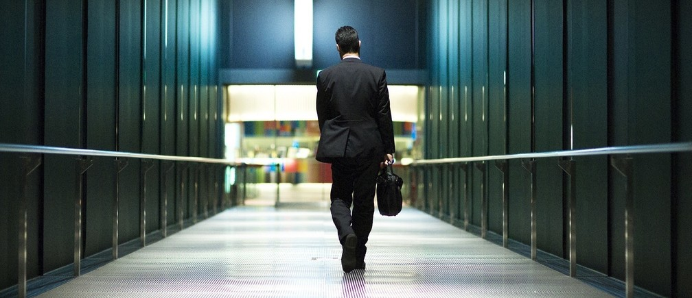 A businessman walks through a banking district.