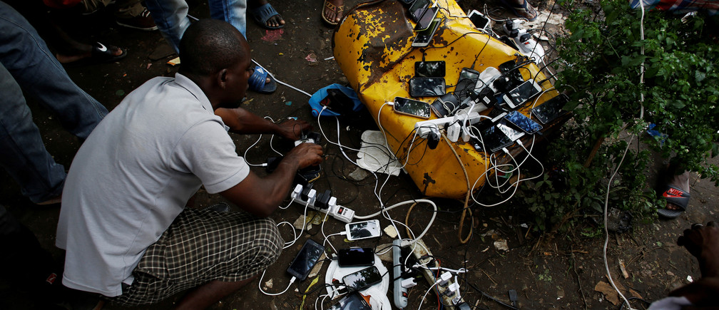 African migrants stranded in Costa Rica charge their phones at a makeshift camp at the border between Costa Rica and Nicaragua, in Penas Blancas, Costa Rica July 15, 2016
