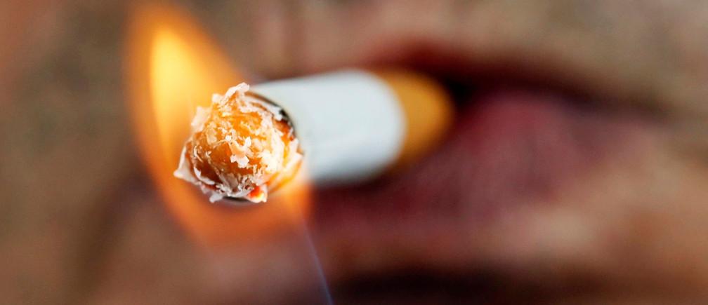 A man lights a cigarette on the street in Brioude, France, June 8, 2018. REUTERS/Regis Duvignau