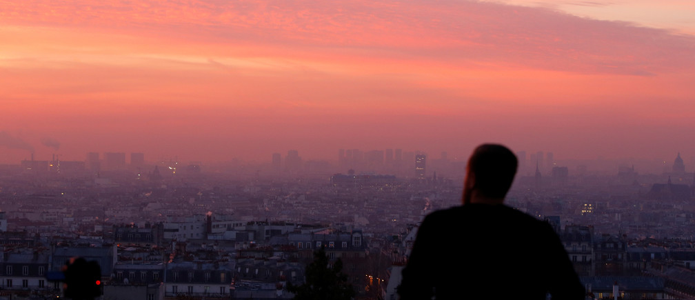 A tourist looks at the sun rises as small-particle haze hangs above the skyline in Paris, France, December 9, 2016 as the City of Light experienced the worst air pollution in a decade.  REUTERS/Gonzalo Fuentes - RTSVCYN