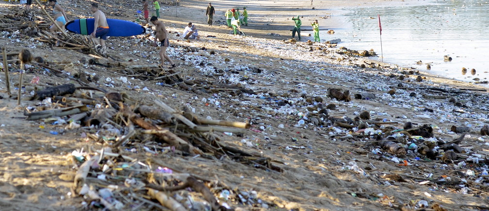 Tourists walk amongst trash washed up on Kuta beach by seasonal winds, as workers attempt a clean-up in the background, on the Indonesian island of Bali February 15, 2016 in this photo taken by Antara Foto.  REUTERS/Wira Suryantala/Antara FotoATTENTION EDITORS - THIS IMAGE HAS BEEN SUPPLIED BY A THIRD PARTY. IT IS DISTRIBUTED, EXACTLY AS RECEIVED BY REUTERS, AS A SERVICE TO CLIENTS. FOR EDITORIAL USE ONLY. NOT FOR SALE FOR MARKETING OR ADVERTISING CAMPAIGNS MANDATORY CREDIT. INDONESIA OUT. NO COMMERCIAL OR EDITORIAL SALES IN INDONESIA.      TPX IMAGES OF THE DAY      - GF10000309242