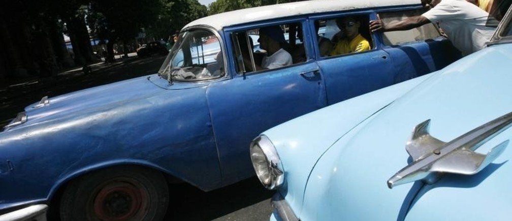 Men push a vintage car used as a taxi in Havana April 26, 2008. Cubans on both sides of the Florida Straits share a love for vintage American cars. In Miami, members of the Cuban community meet once a month to admire the old gas-guzzlers, while in the streets of Havana, 60,000 of those cars are a part of everyday city life