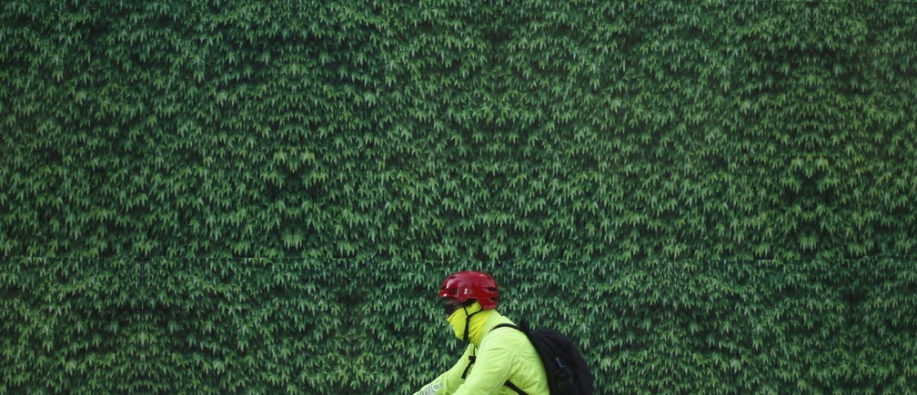A rider cycles with a protective mask in Mexico City, March 15, 2016. Mexico City's government ordered traffic restrictions on Tuesday and recommended people stay indoors due to serious air pollution, issuing its second-highest alert warning for ozone levels for the first time in 13 years. REUTERS/Edgard Garrido - RTSALKM