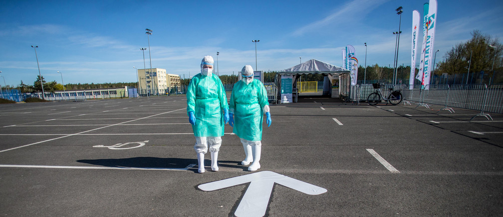 Medical workers stand next to the drive-through mobile testing side for the coronavirus disease (COVID-19) in Bydgoszcz , Poland April 23, 2020.