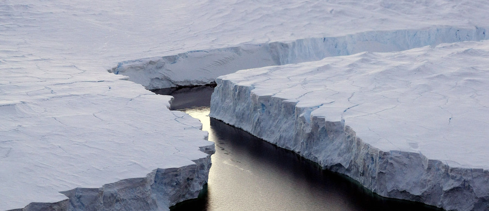 An enormous iceberg (R) breaks off the Knox Coast in the Australian Antarctic Territory, January 11, 2008. Australia's CSIRO's atmospheric research unit has found the world is warming faster than predicted by the United Nations' top climate change body, with harmful emissions exceeding worst-case estimates. Picture taken January 11, 2008.  REUTERS/Torsten Blackwood/Pool    (ANTARCTICA) - RTR1X0U1