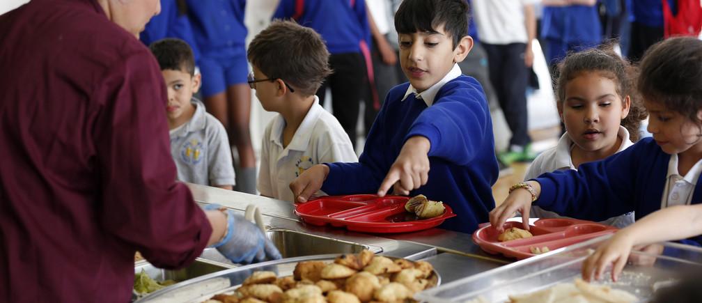 Students receive their lunch at Salusbury Primary School in northwest London June 11, 2014.