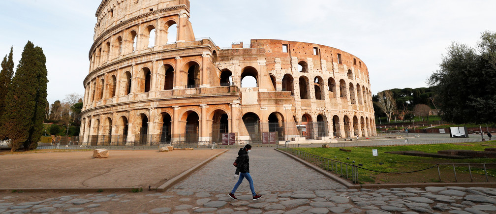 A person wearing a protective mask walks in front the Colliseum, the third day of an unprecedented lockdown across of all Italy imposed to slow the outbreak of coronavirus, in Rome, Italy, March 12, 2020. REUTERS/Guglielmo Mangiapane - RC2HIF9T7XQ8
