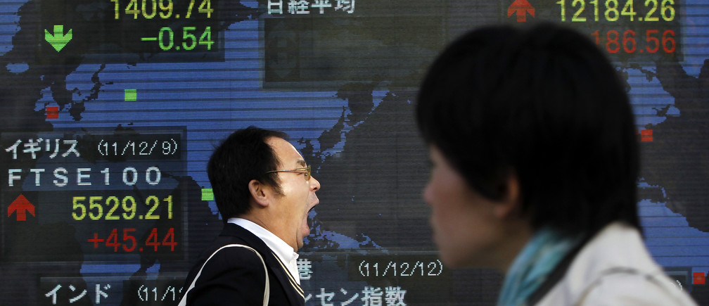 A man yawns as he walks past a stock quotation board outside a brokerage in Tokyo December 12, 2011. Asian stocks gained and the euro steadied on Monday after Europe took a step towards fiscal union, but caution may return as EU leaders failed to stem anxiety over whether their fragile safety net is sufficient to stop the debt crisis from spreading.   REUTERS/Toru Hanai (JAPAN - Tags: BUSINESS) - GM1E7CC0S1K01