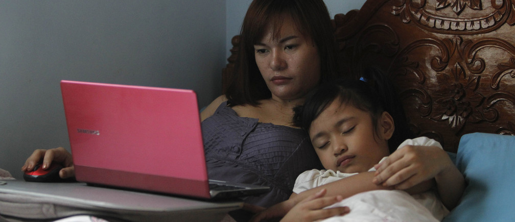 Manila, PhilippinesSheila Ortencio, an online contractor, takes care of her sleeping daughter as she works on her computer inside a bedroom of their house in Lipa city, south of Manila October 5, 2012. Not far from the world of regimented cubicles and headset-toting call centre operators, a quiet revolution is stirring in its slippers. While it's early days, proponents of so-called commercial crowdsourcing contend that a swelling army of global freelancers is already disrupting traditional outsourcing - from preparing tax statements to conducting research on pediatricians. Picture taken October 5, 2012. To match story ASIA-FREELANCE/ REUTERS/Romeo Ranoco